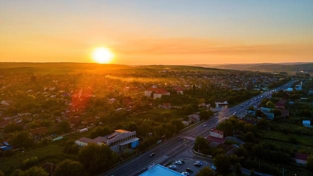 日没時のモルドバ、ティポバの空中ドローンビュー。車、住宅、緑のある道路