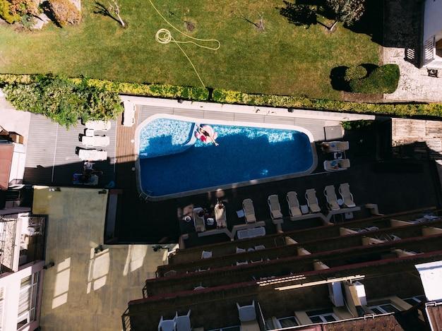 호텔 수영장에서 플라밍고 수영장 플로트에 있는 여성의 공중 무인 항공기 보기