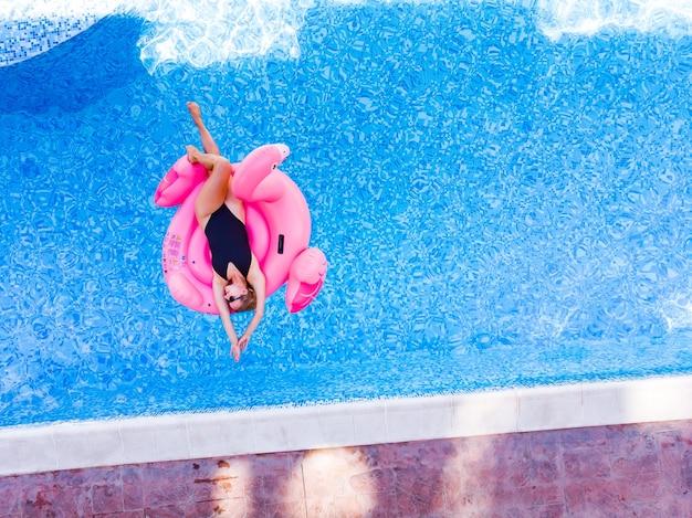 수영장에서 플라밍고 수영장 플로트에 여자의 공중 무인 항공기 보기