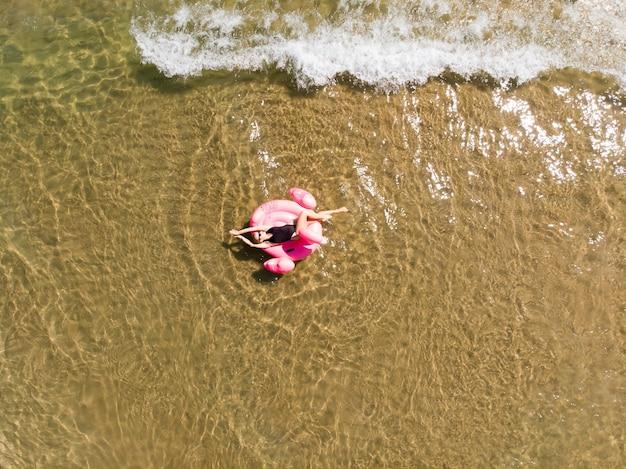 바다에서 플라밍고 풀 플로트에 여자의 공중 무인 항공기 보기