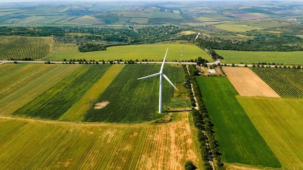 モルドバの村の周りの広いフィールドで稼働している風力タービンの空中ドローンビュー