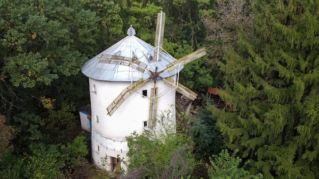 Aerial drone view of an old windmill surrounded by green trees in a forest in moldova