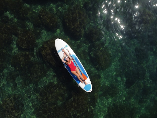 Вид с беспилотника на молодую привлекательную брюнетку с длинными волосами в красном купальнике, плавающую на sup