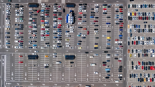 Aerial drone view of parking lot with many cars from above, city transportation and urban concept