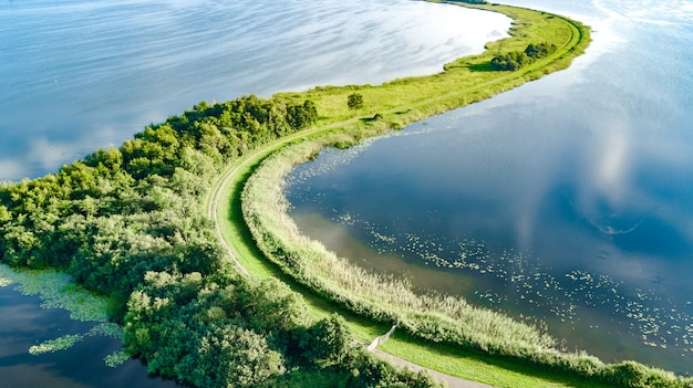 Aerial drone view of path on dam in polder water from above, landscape and nature of north holland, netherlands