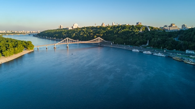 Aerial drone view of pedestrian park bridge, dnieper river and kyiv cityscape from above, city of kiev, ukraine