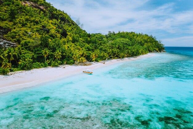 空中ドローンは、セイシェルのマヘ島のテレーズ島にある、ヤシの木と青い澄んだラグーンの孤独な観光船のある絵のように美しいビーチを眺めます。