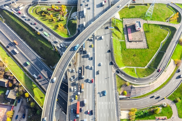 Aerial drone view of road interchange or highway intersection with busy urban traffic in modern city during sunny day. traffic jam aerial view.