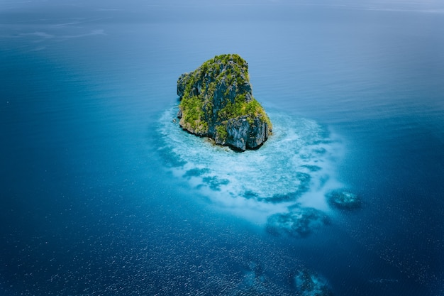 Aerial drone view of a secluded cliff island surrounded by turquoise blue ocean. el nido, palawan.