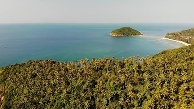 空中ドローンビュー小さなパンガン島、タイ島。エキゾチックな海岸のパノラマ風景、メイハードビーチ、夏の日。サンゴの間の砂の道。鮮やかな海の景色、上からの山の椰子の木。