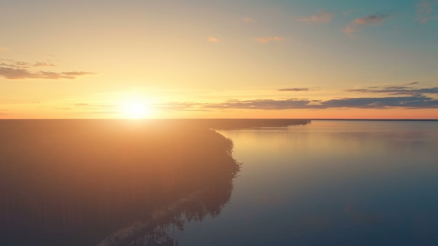Aerial drone view of a sunset over water and forest