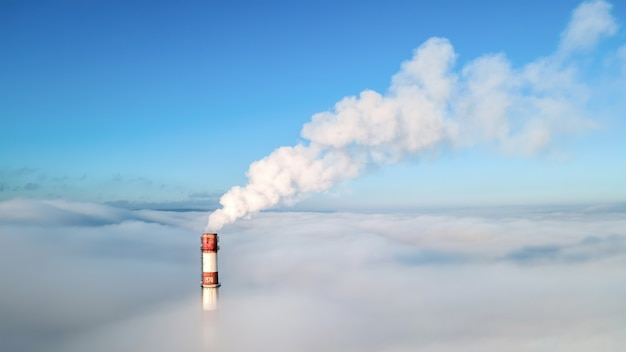 Aerial drone view of thermal station's tube visible above the clouds with smoke coming out. blue and clear sky