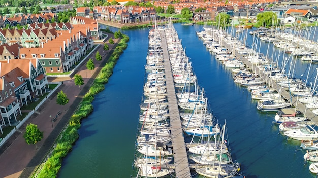 Aerial drone view of typical modern dutch houses and marina in harbor from above, architecture of port of volendam town, north holland, netherlands