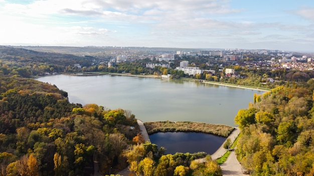 Aerial drone view of valea morilor lake in chisinau. multiple green trees, residential buildings, hills. moldova