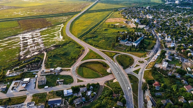 Aerial drone view of a village and road near it, green fields, moldova