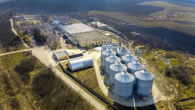 Aerial drone view of a winery metal cisterns with bare trees and fields around it in moldova