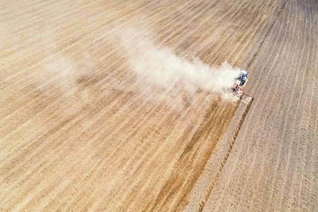 収穫現場で働くトラクターの美しい秋の風景と空中ドローンビュー。農業の概念。