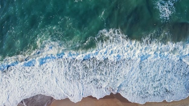 日の出のないターコイズブルーの水と見事な美しい海の風景のビーチのドローンから空中