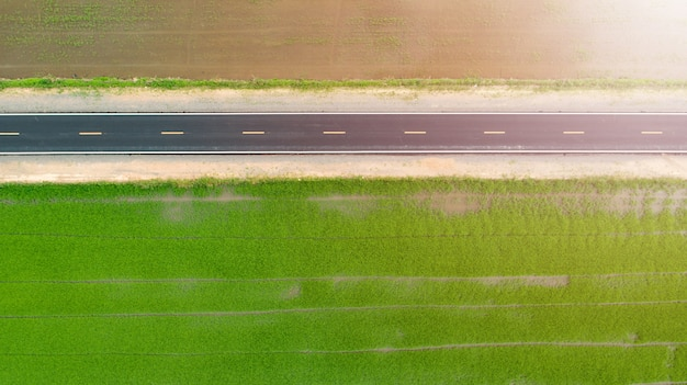 Aerial of green countryside and asphalt road at the top view.