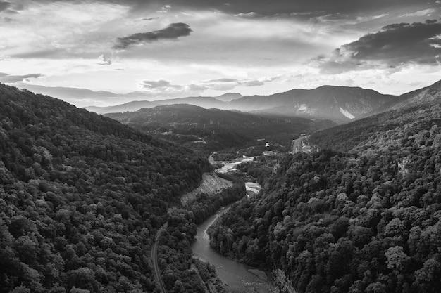 空中グレースケールは曇り空の下で魅惑的な山岳風景を撮影しました