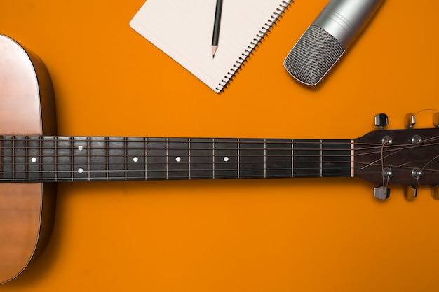Aerial guitar and microphone on color background