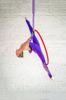 Aerial gymnastics on the circle, a little girl doing exercises