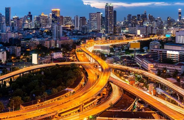 夕焼けの夕暮れ時に超高層ビルのスカイラインとバンコクのダウンタウンの高速道路有料高速道路の空中ハイエンジェルビュー。交通インフラのコンセプト。