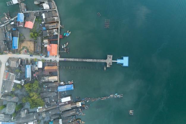 어 부 마을 열 대 바다에 긴 다리의 공중 높은 각도보기 무인 항공기 샷.