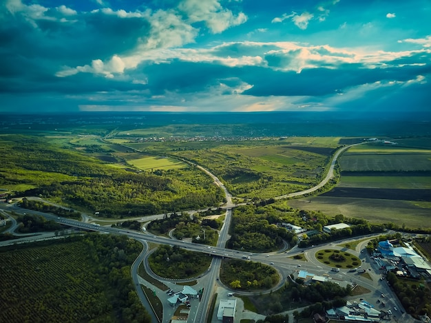 夕方の道路交通上の空中ドローン飛行。高速道路と車やトラックのある高架、インターチェンジ、2レベルの道路の交差点。高速道路、ライン。