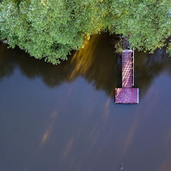 Aerial lake footbridge wooden, lake water and green spring trees with sunshine. photo by drone