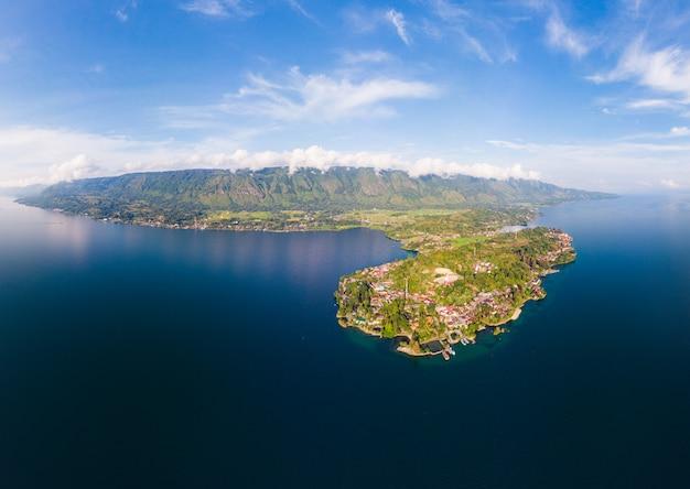 Антенна: озеро тоба и остров самосир, вид сверху суматра индонезия. огромная вулканическая кальдера покрыта водой, традиционные деревни, экваториальный лес.