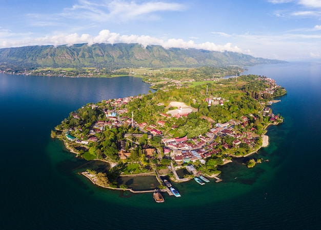 Aerial: lake toba and samosir island view from above sumatra indonesia. huge volcanic caldera covered by water, traditional batak villages, green rice paddies, equatorial forest.