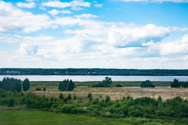 Воздушный пейзаж извилистой реки в зеленом поле, вид сверху на красивый фон природы с дрона, сезонный летний пейзаж с копией пространства