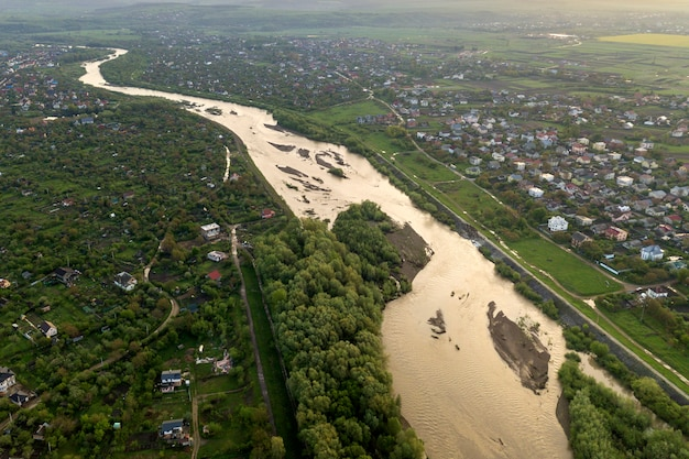 Aerial landscape of small town or village with rows of residential homes and green trees and big flloded river.