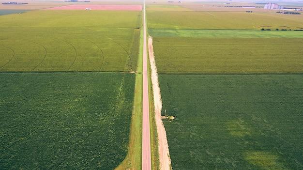 Воздушная длинная прямая дорога, пересекающая поля сельскохозяйственных угодий