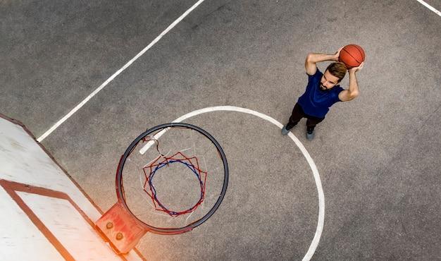 공중선. 남자는 야외에서 거리 농구를 한다. 드론에서 위에서 본 모습.