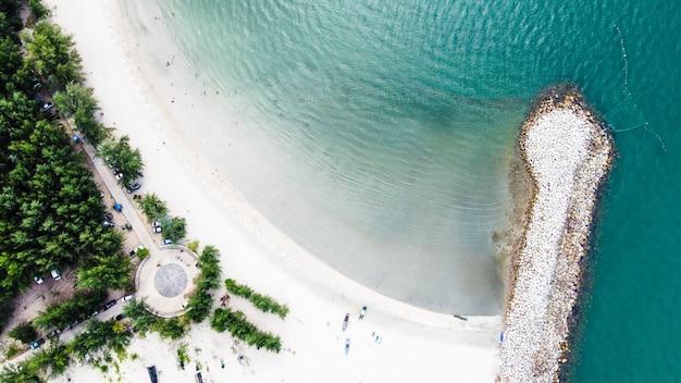 人々のグループと白い砂のビーチ、木々、澄んだ海の水に小さな漁船の景色を望むビーチの防波堤の空中。