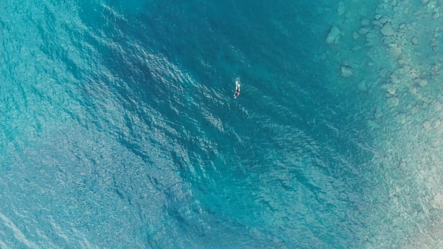Aerial: one person diver swimming fishing in crystal clear mediterranean sea, deep blue transparent water, summer sport vacation concept