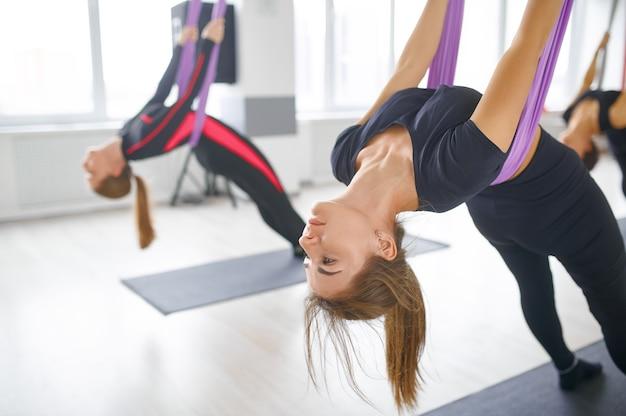 Воздушная или аэро-йога, групповые тренировки, подвешивание на гамаках. фитнес, пилатес и танцевальные упражнения смешивают. женщины на тренировке йоги в тренажерном зале, подходят для образа жизни