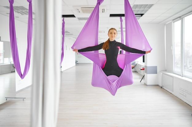 Воздушная или антигравитационная йога, групповые тренировки, подвешивание на гамаках. фитнес, пилатес и танцевальные упражнения смешивают. женщины на тренировке по йоге в тренажерном зале, подходят для образа жизни