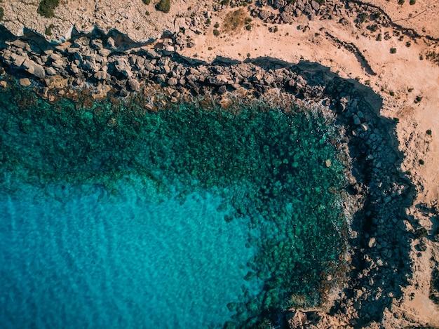 키프로스 케이프 카보 그레코(cape cavo greco) 근처 수정처럼 맑은 푸른 물이 있는 공중 오버헤드 록키 해변