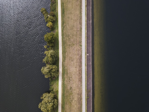 Aerial overhead shot of a brown road near the body of water at daytime