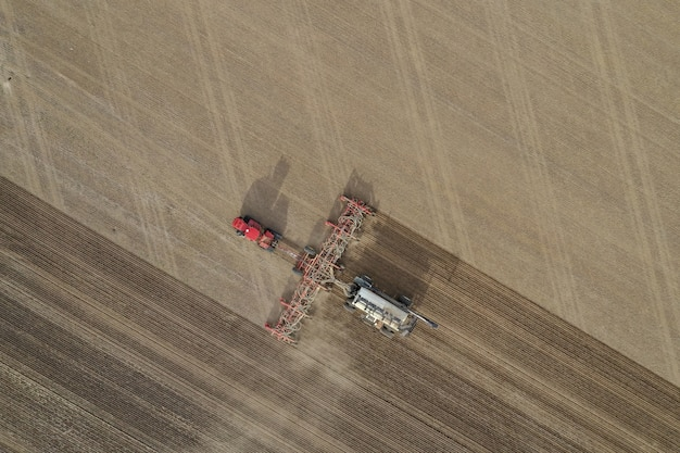Aerial overhead shot of fertilizer machine in a farming field during daytime