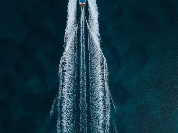 Aerial overhead shot of a motorboat sailing forward in the middle of the ocean