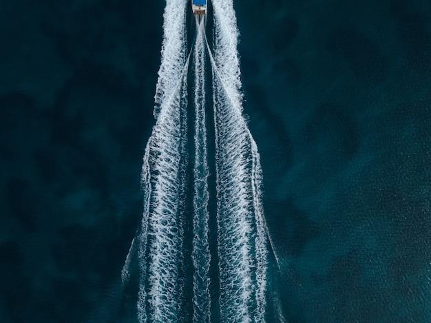 海の真ん中で前進するモーターボートの空中オーバーヘッドショット
