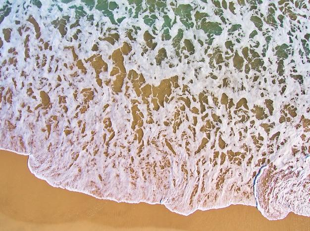 オレンジ色の砂と緑の水と海の波の泡の空中オーバーヘッドショット