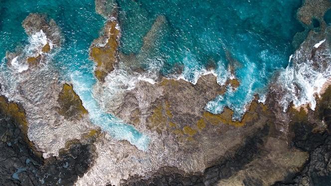 Aerial overhead shot of sea with rocky coastline