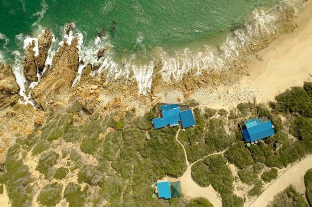 Ripresa aerea dall'alto di una spiaggia con acqua turchese pura e lodge durante il giorno