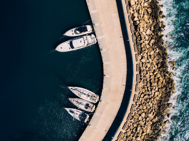 Aerial overhead shot of white sailboats docked on the coast of the ocean