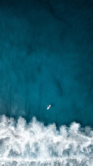 Aerial overhead vertical shot of beautiful ocean waves with a plane flying above